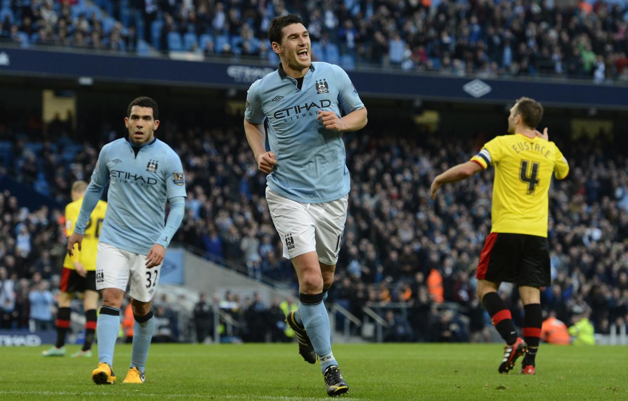 """Manchester City's English midfielder Gareth Barry (C) celebrates after scoring the second goal during the English FA Cup third round football match between Manchester City and Watford at The Etihad stadium in Manchester, north-west England on January 5, 2013. AFP PHOTO/PAUL ELLIS  RESTRICTED TO EDITORIAL USE. No use with unauthorized audio, video, data, fixture lists, club/league logos or """"live"""" services. Online in-match use limited to 45 images, no video emulation. No use in betting, games or single club/league/player publications.PAUL ELLIS/AFP/Getty Images"""