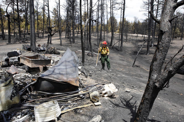 Firefighter Brandie Smith from Salida, Colo., walks past a burned out structure on the Black Forest wildfire north of Colorado Springs, Colo., on Monday, June 17, 2013. Over 470 homes burned in the wildfire that started last Tuesday. (AP Photo/Ed Andrieski)