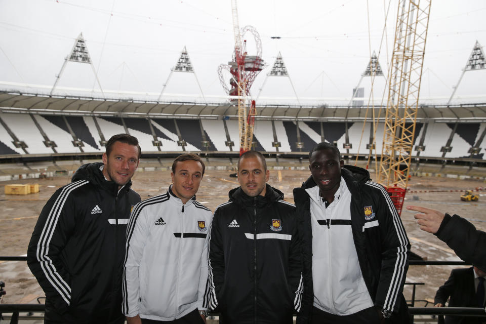 <p> West Ham United Football Club players from left, captain Kevin Nolan, Mark Noble, Joe Cole and Mohamed Diame pose for the photographers at the Olympic Stadium in London, Wednesday, Nov. 20, 2013. Construction continues in Queen Elizabeth Olympic Park's Stadium to transform it into a year round multi-use venue, the permanent home of West Ham United Football Club and the new national competition stadium for UK Athletics. (AP Photo/Lefteris Pitarakis)</p>