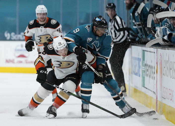 Anaheim Ducks left wing Andrew Agozzino (26) battles for the puck against San Jose Sharks left wing Evander Kane (9) during the first period of an NHL hockey game Monday, April 12, 2021, in San Jose, Calif. (AP Photo/Tony Avelar)