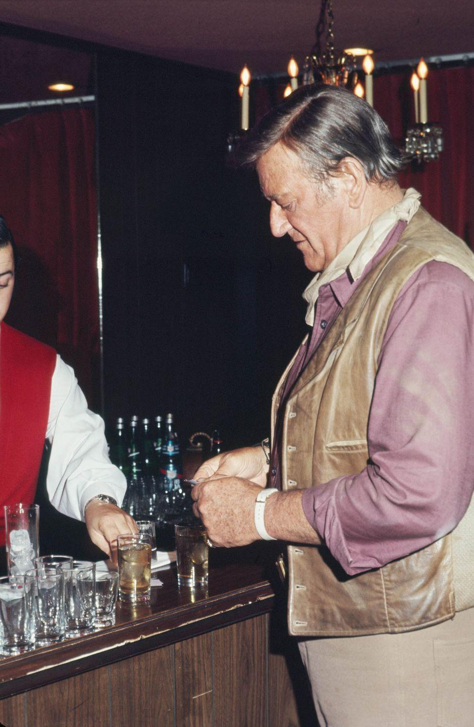 <p>John Wayne buys a few drinks at a charity costume party in July 1971 in Los Angeles, California.</p>