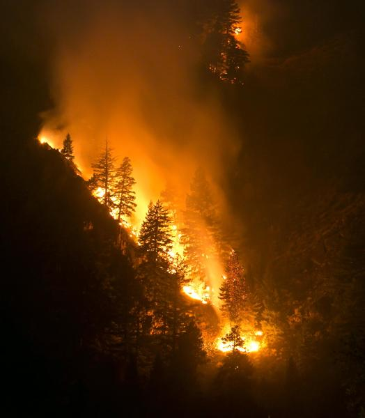 Fire creeps slowing down the western canyon wall above the Wood River in Hailey where firefighters continue to battle the Beaver Creek Fire Saturday Aug. 17, 2013. (AP Photo/Idaho Statesman, Darin Oswald)