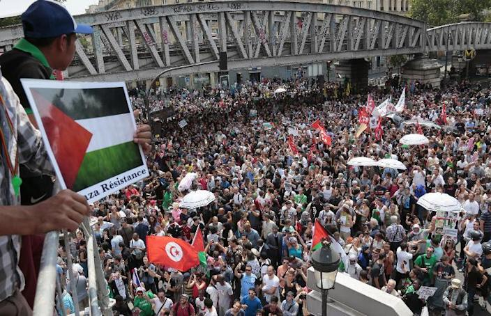 A protester standing on a scaffolding holds a placard depicting the Palestinian flag as protestors gather near the Barbes-Rochechouart metro station in Paris on July 19, 2014 (AFP Photo/Jacques Demarthon)