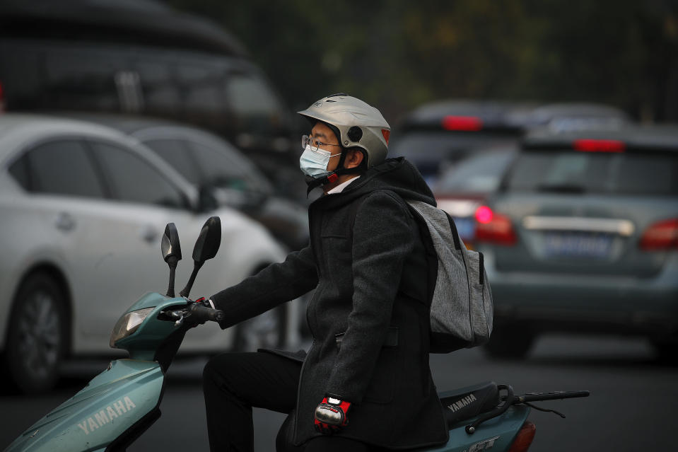 A man wearing a face mask to help curb the spread of the coronavirus rides on a scooter as he waits to cross a street during the morning rush hour in Beijing, Monday, Oct. 26, 2020. Schools and kindergartens have been suspended and communities are on lockdown in Kashgar, a city in China's northwest Xinjiang region, after more than 130 asymptomatic cases of the coronavirus were discovered. (AP Photo/Andy Wong)