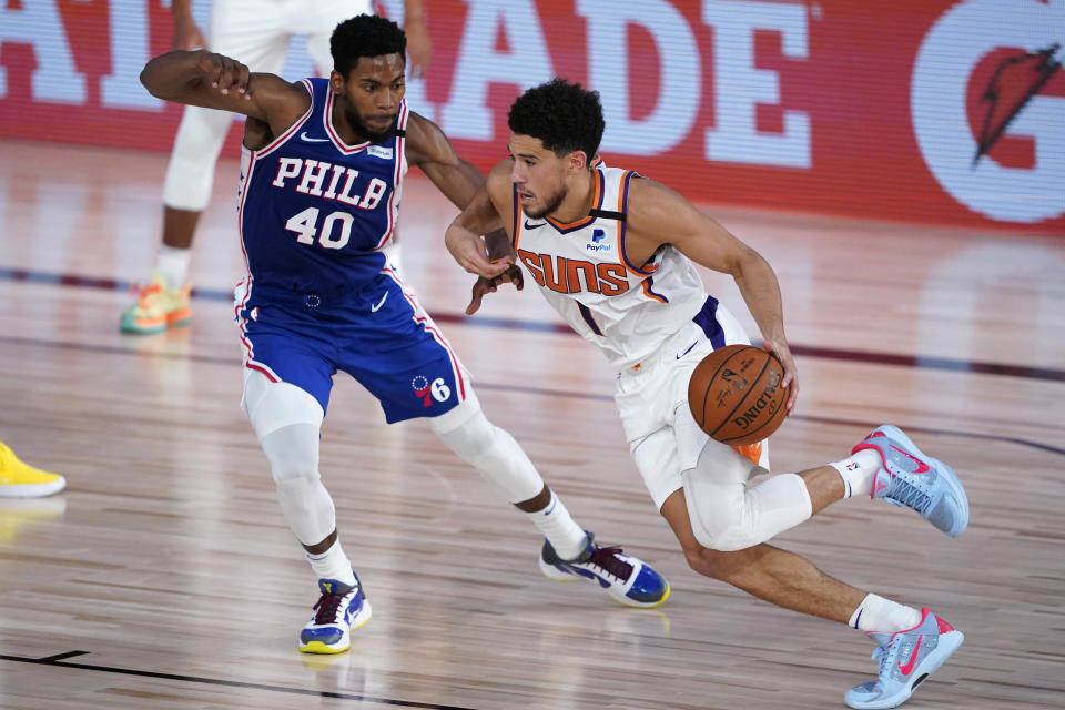 Devin Booker #1 of the Phoenix Suns drives against Glenn Robinson III #40 of the Philadelphia 76ers during a game on Aug. 11, 2020. (Ashley Landis-Pool/Getty Images)