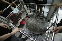 """The female green green turtle nicknamed """"Bank"""" is carried after her surgery at Chulalongkorn University's veterinary faculty in Bangkok, Thailand, Monday, March 6, 2017. Veterinarians operated Monday on """"Bank,"""" removing less than 1,000 coins from the endangered animal. Her indigestible diet was a result of many tourists seeking good fortune tossing coins into her pool over many years in the eastern town of Sri Racha. (AP Photo/Sakchai Lalit)"""