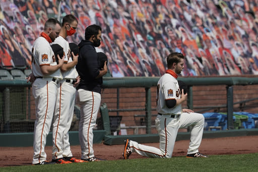 San Francisco Giants' Austin Slater, right, kneels during the national anthem before a baseball game between the Giants and the Arizona Diamondbacks in San Francisco, Sunday, Sept. 6, 2020. (AP Photo/Jeff Chiu)