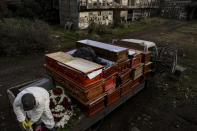 Workers collect the coffins of people that have been recently cremated amid the new coronavirus pandemic, at the La Recoleta cemetery in Santiago, Chile, Sunday, June 28, 2020. The coffins are collected, destroyed, and processed by a company specialized in organic waste. (AP Photo/Esteban Felix)