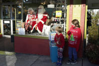 Beckett, right, and Hudson Gravley stand on the sidewalk in front of a storefront to pose for a photo with Santa and his wife, Mrs. Claus, in Bellingham, Wash., on Dec. 12, 2020. The storefront Santa sits on Saturday's during this holiday season in the shop window, where children can drop letters in a box outside and pose for photos as Santa sits inside behind. In this socially distant holiday season, Santa Claus is still coming to towns (and shopping malls) across America but with a few 2020 rules in effect. (AP Photo/Elaine Thompson)