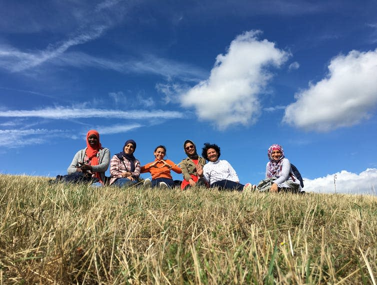 A group of women sit smiling in a field.
