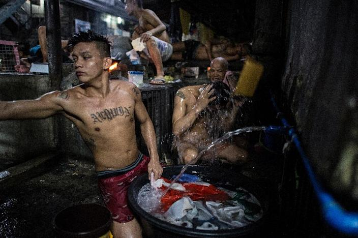 An inmate (C-top) cooks his dinner as other detainees take a bath inside the Quezon City Jail in Manila (AFP Photo/Noel Celis)
