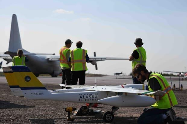 A crew member for the Alaska Center for Unmanned Aircraft Systems Integration takes a last minute maintenance check on the SeaHunter, the Unmanned Aircraft System used to take photos of the highway between Inuvik to Tuktoyaktuk, and portions of the Dempster Highway. (Alaska Center for Unmanned Aircraft Systems Integration - image credit)