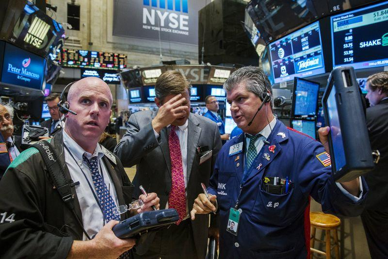 Traders attempt to figure out what is happening as trading resumes following a several hour long stoppage on the floor of the New York Stock Exchange in New York