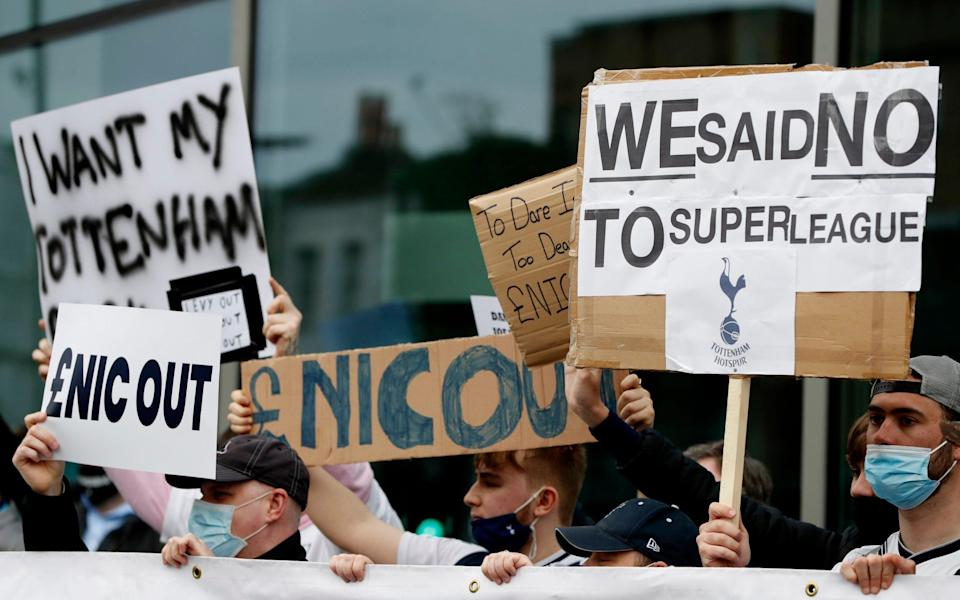 Tottenham fans hold banners protesting against the board outside the stadium - Reuters