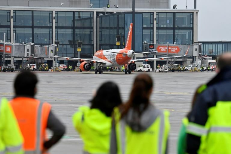 Airport workers look on as the Easyjet plane, one of the first two flights to arrive, taxis to a stop in front of the main terminal