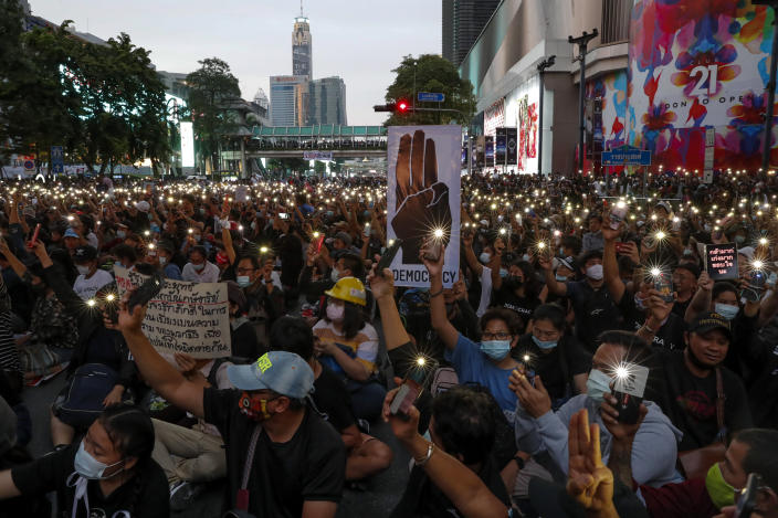 Pro-democracy activists wave their mobile phone flash lights during a protest rally at Ratchaprasong business district in Bangkok, Thailand, Sunday, Oct. 25, 2020. Pro-democracy protesters in Thailand gathered again Sunday in Bangkok, seeking to keep up pressure on the government a day ahead of a special session of Parliament called to try to ease political tensions.(AP Photo/Gemunu Amarasinghe)