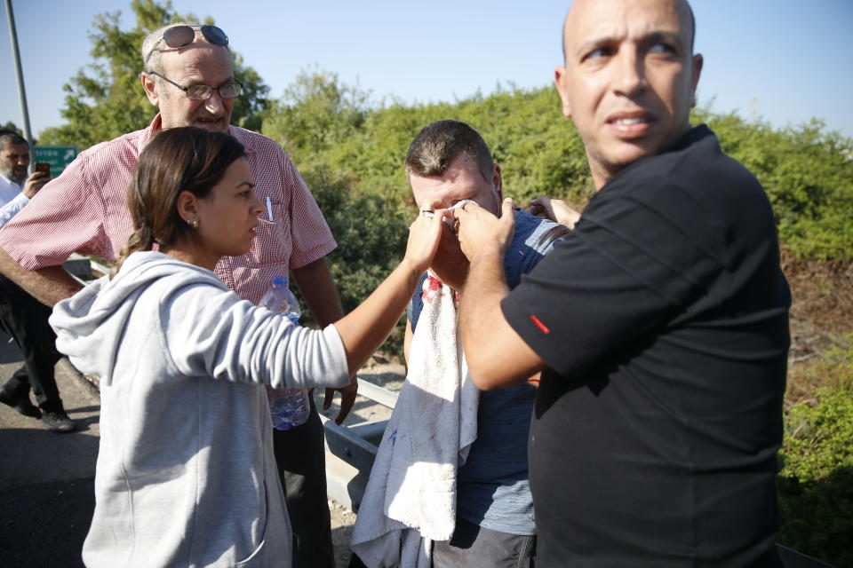 People treat a wounded man after a rocket fired by Palestinians militants from Gaza hit a main free way between Ashdod and Tel Aviv, near Ashdod Israel , Nov.12 2019. srael has killed a senior Islamic Jihad commander in Gaza in a rare targeted killing that threatened to unleash a fierce round of cross-border violence with Palestinian militants. (AP Photo/Ariel Schalit)