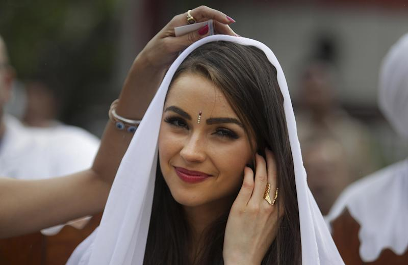FILE- In this, Sept. 30, 2013 file photo, Miss Universe Olivia Culpo, watches a performance by inmates as designer Sanjana Jon, adjusts her veil during a visit to the Tihar Jail in New Delhi, India. Indian police say they have filed a case against American Olivia Culpo, for an unauthorized footwear fashion shoot at the Taj Mahal, India's white-marble monument to love. Police Inspector Sushant Gaur said they shot a commercial for footwear at the Taj Mahal on Sunday without the permission of the state-run Archaeological Survey of India. (AP Photo/Tsering Topgyal, file)