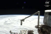 In this image made from NASA TV, the SpaceX Crew Dragon spacecraft is seen with the Earth behind from the international space station, Saturday, April 24, 2021. The recycled SpaceX capsule carrying four astronauts has arrived at the International Space Station, a day after launching from Florida. (NASA via AP)