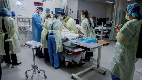PHOTO: Medical workers help a patient in the emergency room at Riverside University Health System in Moreno Valley, Calif., June 26, 2020. (Orange County Register via ZUMA Press)