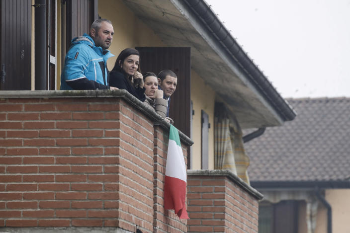 People follow the unveiling of a memorial for Covid deaths in Codogno, northern Italy, Sunday, Feb. 21, 2021. The first case of locally spread COVID-19 in Europe was found in the small town of Codogno, Italy one year ago on February 21st, 2020. The next day the area became a red zone, locked down and cutoff from the rest of Italy with soldiers standing at roadblocks keeping anyone from entering of leaving. (AP Photo/Luca Bruno)