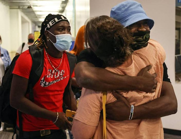 On Thursday, July 15, 2021, brothers Lovinsky, 27, left, and John Nalus, 21, right, is greeted by a family friend, Randy Kurtz, center, upon their arrival in the United States after being detained in the Dominican Republic just short of a year on an alleged drug charge.