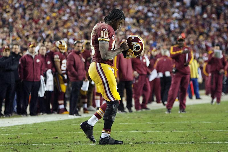 In this Jan. 6, 2013, photo, Washington Redskins quarterback Robert Griffin III (10) returns to the huddle after hurting his right knee as he fell awkwardly while throwing an incomplete pass during the first quarter of their NFL wild card playoff football game against the Seattle Seahawks in Landover, Md. An injury that sidelines Griffin well into next season is a very real possibility _ or at least it seemed that way Monday, Jan. 7, after head coach Mike Shanahan described the results of tests on the rookie's right knee following a series of plays in their Sunday game that did additional damage to a knee that was just three games removed from suffering a sprained lateral collateral ligament. (AP Photo/The Virginian-Pilot, L. Todd Spencer) MAGS OUT