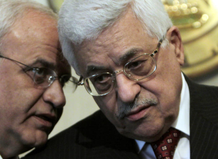 FILE - In this Dec. 28, 2008 file photo, Palestinian President Mahmoud Abbas, right, consults with his aide Saeb Erekat, during a press conference at the Presidential palace in Cairo, Egypt. Erekat, a veteran peace negotiator and prominent international spokesman for the Palestinians for more than three decades, died Tuesday, Nov. 10, 2020. He was 65. (AP Photo/Amr Nabil, File)