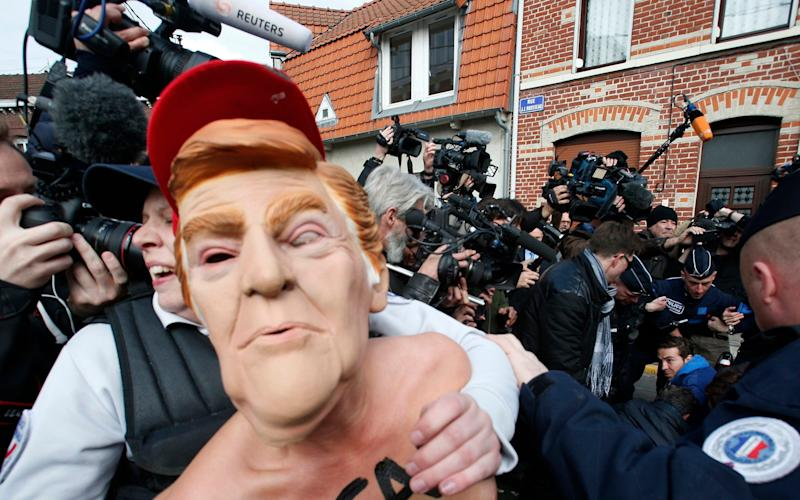 A Femen activist wearing the mask of U.S President Donald Trump is detained as she demonstrates in Henin-Beaumont, northern France, where far-right leader and presidential candidate Marine Le Pen was voting - Credit: AP