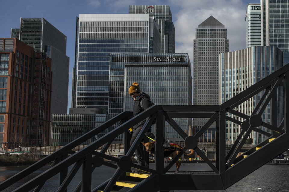 A woman walk her dog over a bridge near the Canary Wharf business district. Photo: Dan Kitwood/Getty Images