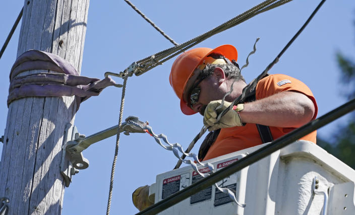 FILE - In this Wednesday, Aug. 4, 2021, file photo, Travis Sheetz, a worker with the Mason County (Wash.) Public Utility District, installs fiber optic cable on a utility pole, while working with a team to bring broadband internet service to homes in a rural area surrounding Lake Christine near Belfair, Wash. (AP Photo/Ted S. Warren, File)