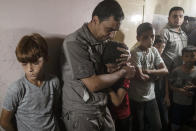 Relatives of Palestinian Omar al-Nile, 12, who was shot on Saturday during a violent demonstration on the eastern border between Gaza and Israel, react during his funeral in the family home in Gaza City, Saturday, Aug. 28, 2021. (AP Photo/Khalil Hamra)