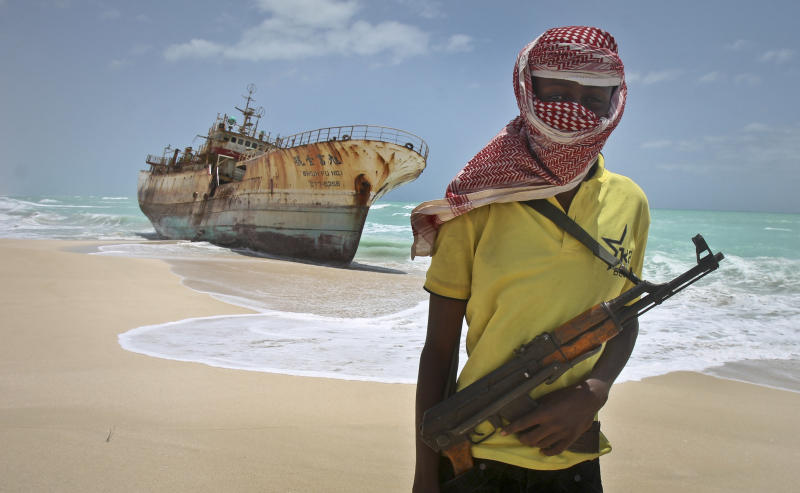 FILE - In this Sunday, Sept. 23, 2012 file photo, masked Somali pirate Hassan stands near a Taiwanese fishing vessel that washed up on shore after the pirates were paid a ransom and released the crew, in the once-bustling pirate den of Hobyo, Somalia. World sea piracy fell for a third straight year in 2013, as Somali pirates were curbed by international naval patrols and improved ship vigilance, an international maritime watchdog said Wednesday, Jan. 15, 2014. (AP Photo/Farah Abdi Warsameh, File)