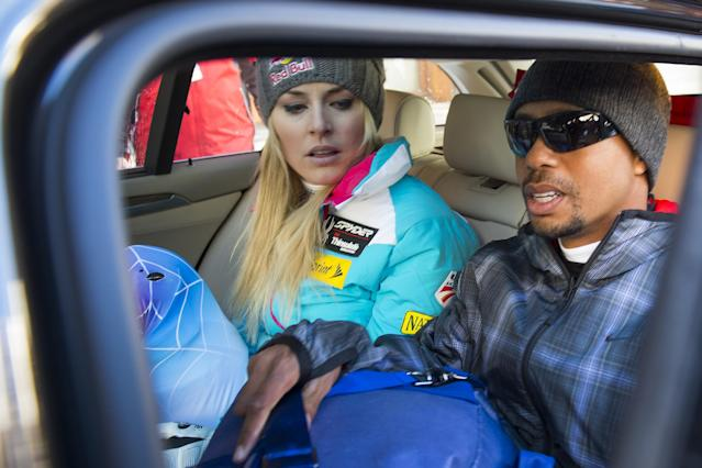 Lindsey Vonn of the US, left, and boyfriend Tiger Woods, right, leave the finish area during the women's Downhill race of the FIS Alpine Ski World Cup season, in Val d'Isere, France, Saturday, Dec. 21, 2013. (AP Photo/Keystone,Jean-Christophe Bott)