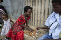 Elena, 7, left, plays a game of checkers using soda bottle tops with friend Hailemariam, 12, right, at a reception and day center for displaced Tigrayans in Mekele, in the Tigray region of northern Ethiopia Sunday, May 9, 2021. The Tigray conflict has displaced more than 1 million people, the International Organization for Migration reported in April, and the numbers continue to rise. (AP Photo/Ben Curtis)