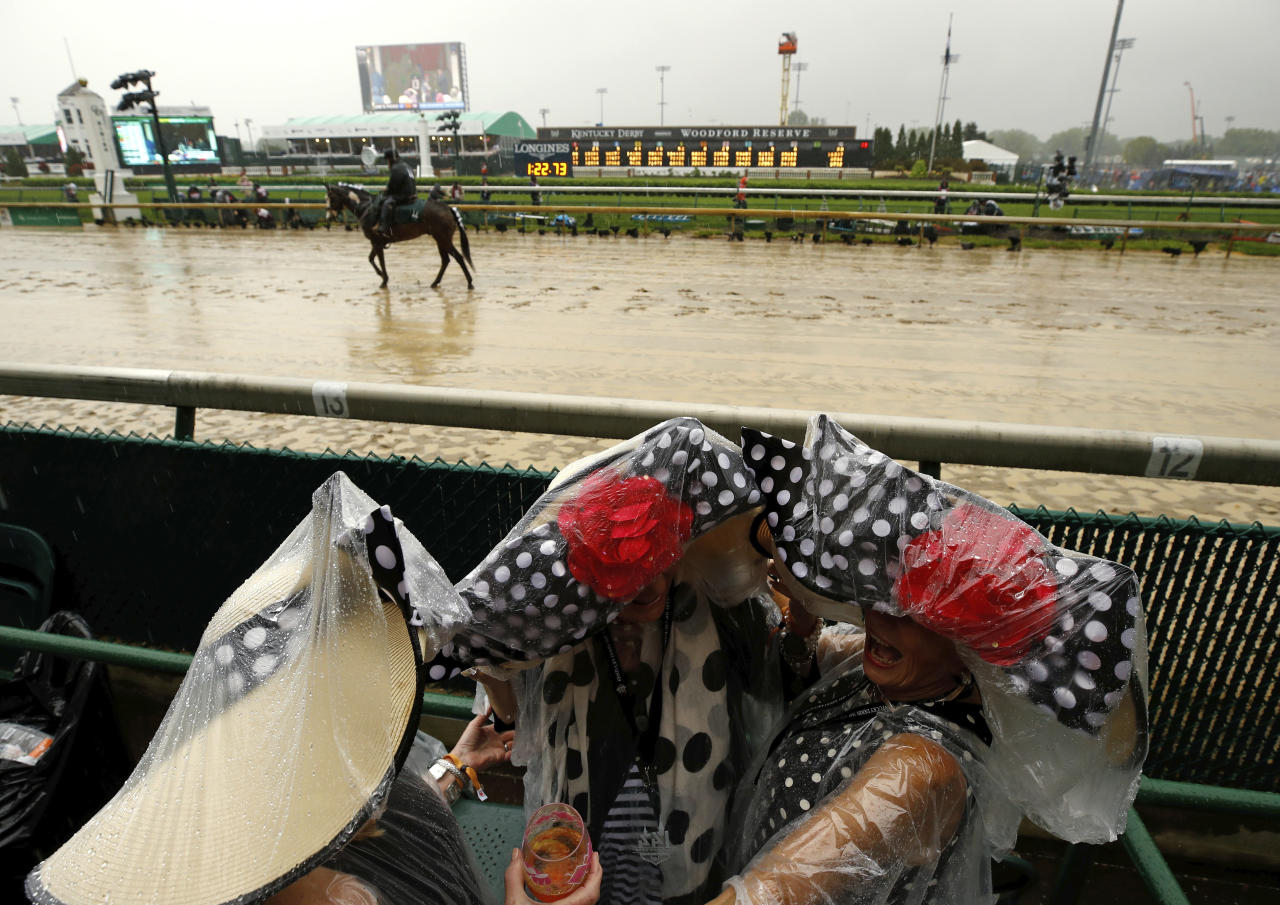 <p>Fans huddle under plastic before the 144th running of the Kentucky Derby horse race at Churchill Downs Saturday, May 5, 2018, in Louisville, Ky. (Photo: Charlie Riedel/AP) </p>