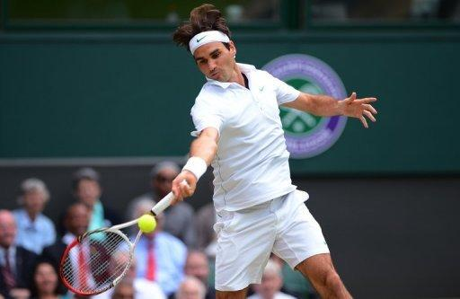 Switzerland's Roger Federer plays a forehand shot during his men's singles quarter-final against Russia's Mikhail Youzhny at Wimbledon on Wednesday. Defending champion Novak Djokovic and six-time winner Roger Federer face a titanic Wimbledon semi-final showdown after the two title contenders wasted little time on their last eight matches on Wednesday