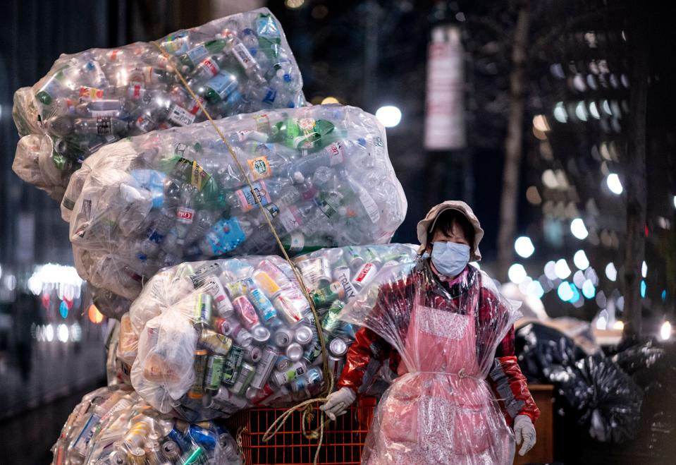 A woman wearing a face mask and a plastic bag pulls a cart loaded with bags of recyclables through the streets of Lower Manhattan during the outbreak of the novel coronavirus (which causes COVID-19) on April 16, 2020 in New York City. (Photo by Johannes EISELE / AFP) (Photo by JOHANNES EISELE/AFP via Getty Images)