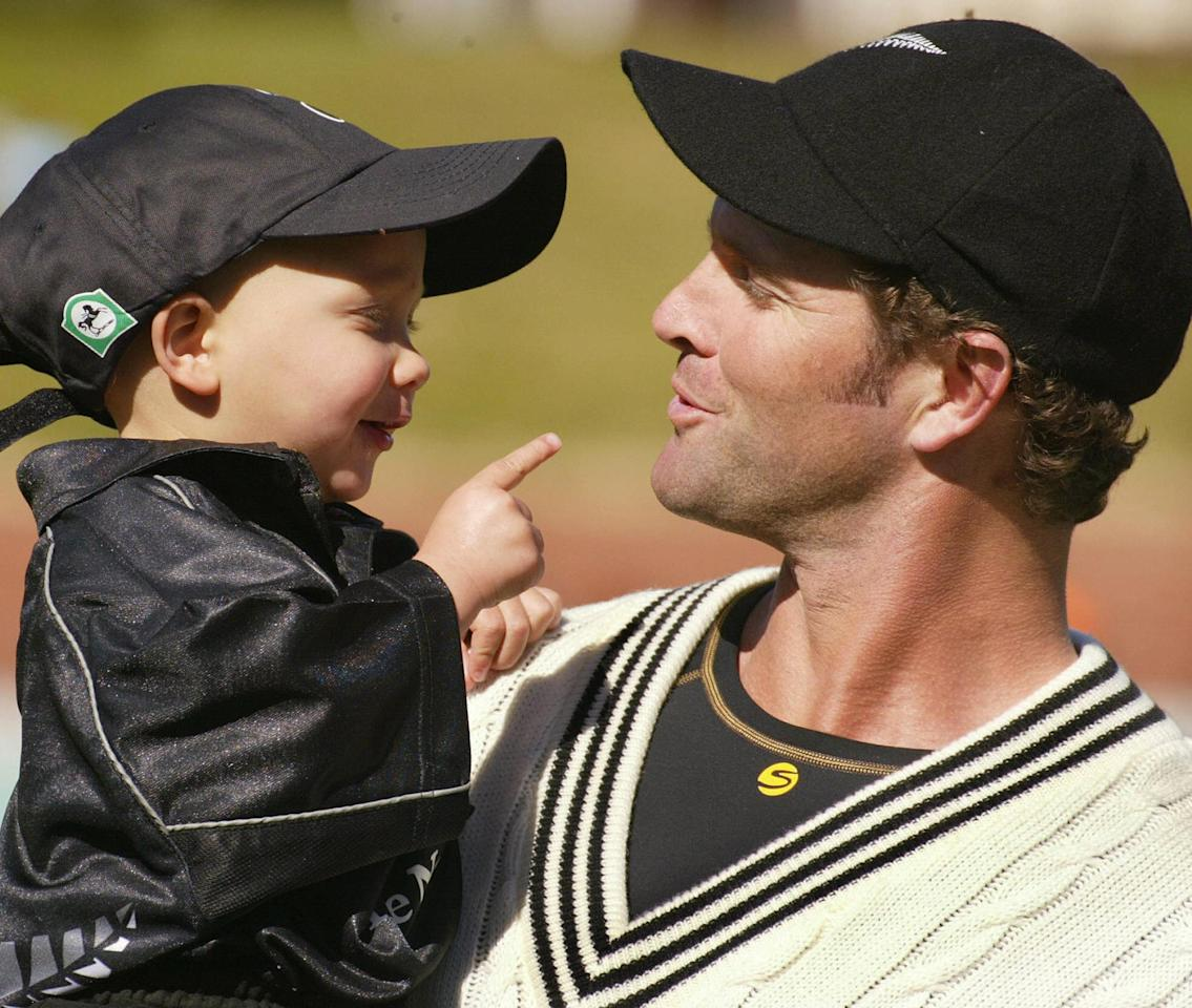 New Zealand all-rounder Chris Cairns (R) enjoys a lighter moment with his son Thomas (L), Wellington, 30 March 2004. (WILLIAM WEST/AFP/Getty Images)