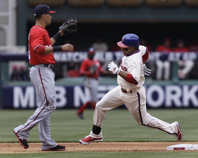 Philadelphia Phillies' Ben Revere rounds second base on a triple as Washington Nationals' Ian Desmond waits for the ball in the third inning of a baseball game, Sunday, May 4, 2014, in Philadelphia. (AP Photo/Laurence Kesterson)