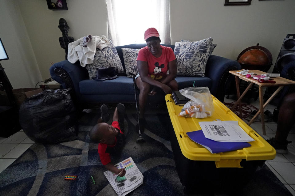 Natasha Blunt sits in her apartment with her grandson Kamille Blunt, 5, in the aftermath of Hurricane Ida in Chalmette, La., Monday, Sept. 6, 2021. Before the hurricane hit, the New Orleans native had hardly recovered from facing eviction and loss of her catering job during the pandemic. The storm, which left her in the dark and without power for several days, has taken Blunt to the brink. Unable to work as her health deteriorates from a pair of strokes, Blunt is still facing eviction while she cares for Kamille. (AP Photo/Gerald Herbert)