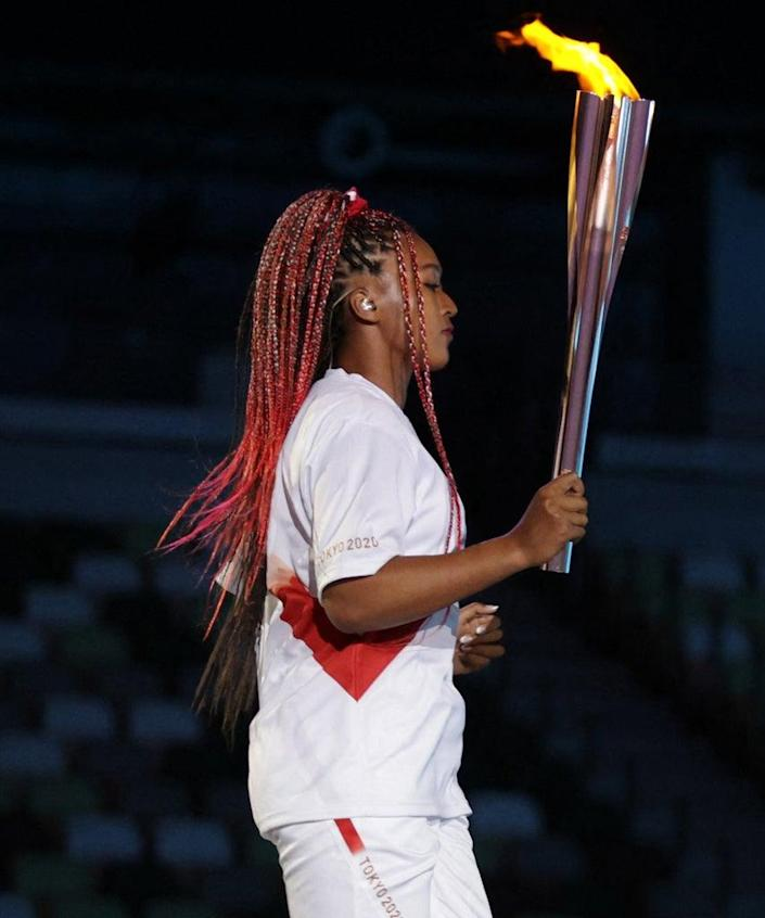 Japanese tennis player Naomi Osaka holds the Olympic Torch before lighting the flame of hope in the Olympic Cauldron during the opening ceremony of the Tokyo 2020 Olympic Games, at the Olympic Stadium, in Tokyo, on July 23, 2021. (Photo by HANNAH MCKAY / POOL / AFP) (Photo by HANNAH MCKAY/POOL/AFP via Getty Images)