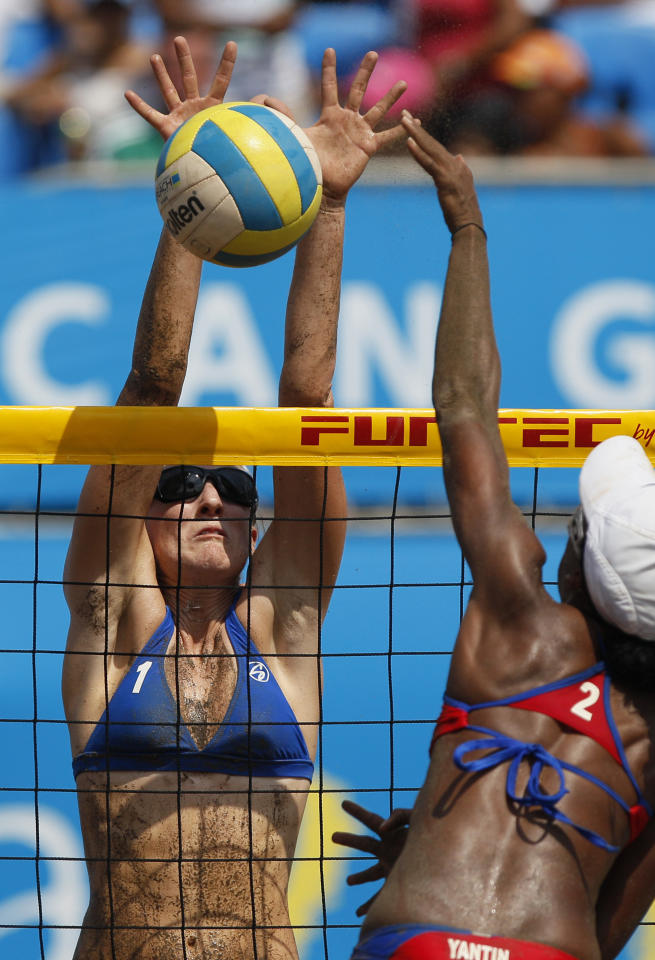 Emily Day, of the United States, left, spikes the ball as Puerto Rico's Yamileska Yantin tries to block during the women's beach volleyball bronze medal match at the Pan American Games in Puerto Vallarta, Mexico, Friday, Oct. 21, 2011. (AP Photo/Ariana Cubillos)