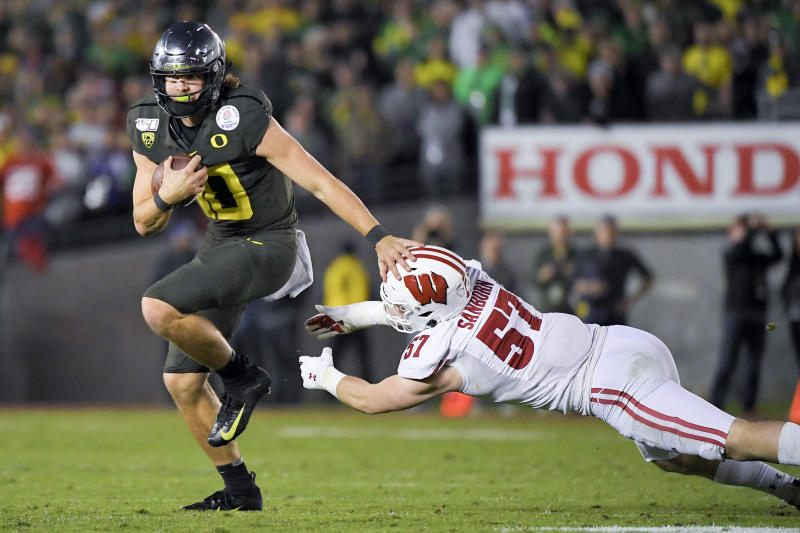 Oregon quarterback Justin Herbert runs for a touchdown past Wisconsin linebacker Jack Sanborn during second half of the Rose Bowl NCAA college football game Wednesday, Jan. 1, 2020, in Pasadena, Calif. (AP Photo/Mark J. Terrill)
