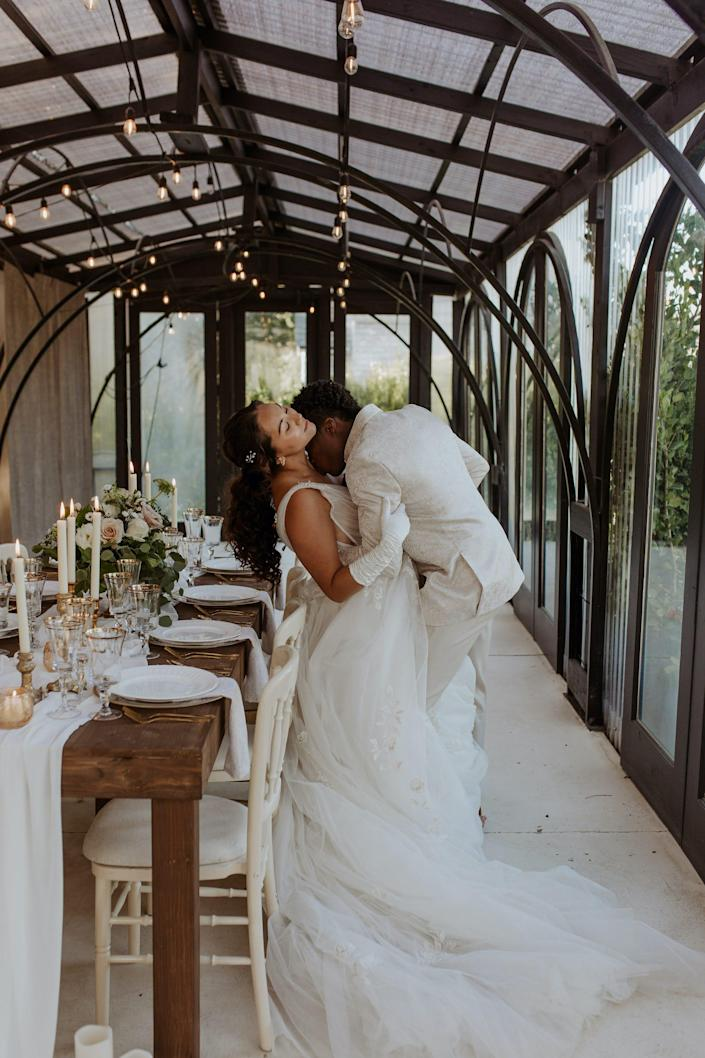 A groom kisses a bride's neck as they lean against a table in a room made of windows.