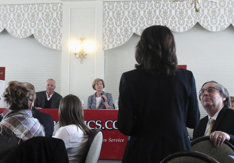 FILE - In this Feb. 22, 2018, file photo, Republican Senate candidate Leah Vukmir, standing, asks a question of Democratic U.S. Sen. Tammy Baldwin during a luncheon in Madison, Wis. Vukmir faces Baldwin in one of the most expensive Senate races in the country. (AP Photo/Scott Bauer, File)