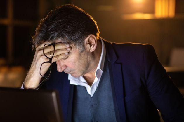 Tired businessman with eyes closed, feeling headache, trying to stay concentrated for late night work at office (Photo: miodrag ignjatovic via Getty Images)