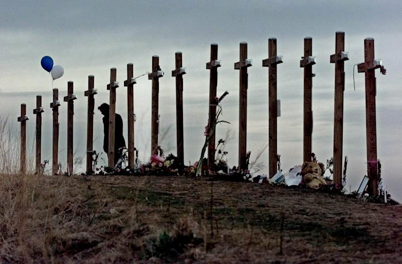 FILE - In this April 28, 1999, file photo, a woman stands among 15 crosses posted on a hill above Columbine High School in Littleton, Colo.
