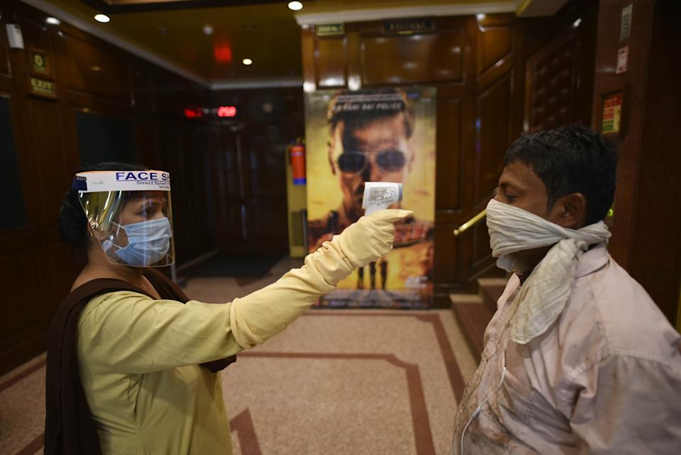 NEW DELHI, INDIA - OCTOBER 13: An employee wearing a face-shield on duty thermally screens a man during preparation for reopening of cinema halls amid the spread of coronavirus, at Delhi Gate on October 13, 2020 in New Delhi, India. Multiplexes and cinema halls have been allowed to reopen from October 15, with up to 50 per cent of their seating capacity, under Unlock 5.0. Standard operating procedures (SOPs) have been issued by the central government. (Photo by Vipin Kumar/Hindustan Times via Getty Images)