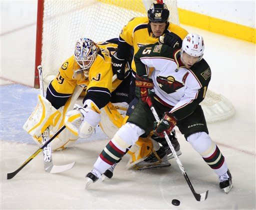 Minnesota Wild right wing Dany Heatley (15), controls the puck in front of Nashville Predators defenseman Ryan Suter (20) and goalie Anders Lindback (39), of Sweden, during the second period of an NHL hockey game on Tuesday, April 3, 2012, in Nashville, Tenn. (AP Photo/Mike Strasinger)